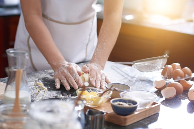 Unrecognizable woman standing at kitchen table and kneading dough by hand