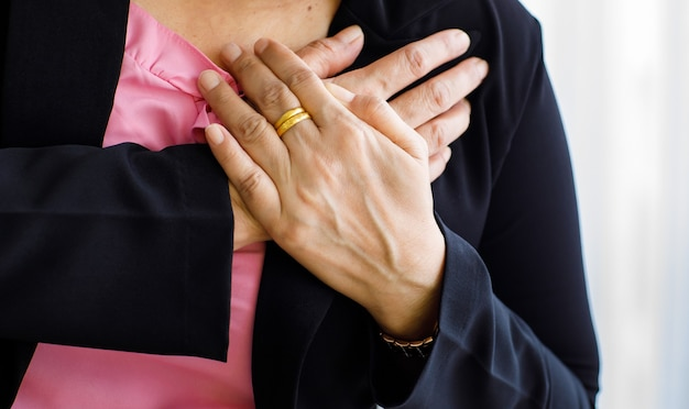 Unrecognizable woman suffering from sudden heart attack and hold chest. concept of emergency health care and affected from congestive failure or cardiopulmonary resuscitation, heart problem.