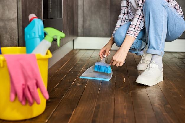 인식 할 수없는 여자 브러시와 쓰레받기 빗자루를 들고 쓰레받기로 먼지를 모으는 바닥 청소