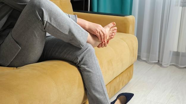 알아볼 수 없는 여성이 신발을 벗고 소파에 앉아 발 마사지를 합니다.