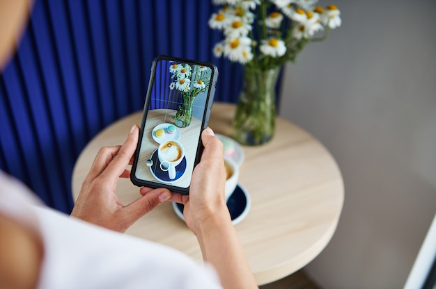 スタイリッシュな喫茶店でマカロンとコーヒーラテまたはカプチーノのカップと一緒に出されたテーブルの食べ物の写真を撮っている認識できない女性。ライブビューモードの携帯電話。静物