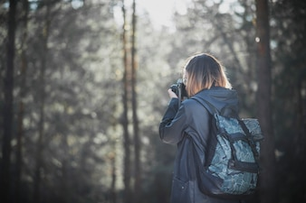 Unrecognizable woman taking pictures of forest