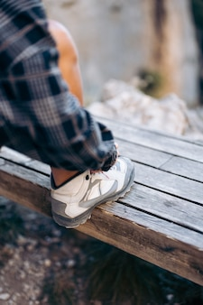 Unrecognizable woman tying laces of hiking shoes