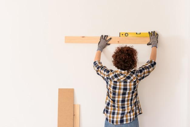 인식 할 수없는 여성은 수평계를 사용하여 자연광이있는 아파트 내부의 흰색 벽에 나무 판자를 정확하게 배치합니다.