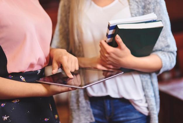 図書館でデジタルタブレットを使用している認識できない女性