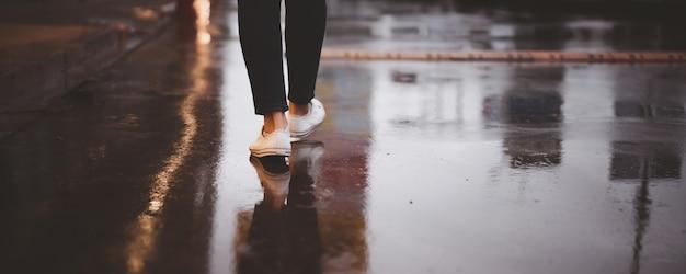 雨が降っている間、長い通りを歩いている認識できない女性、暴風雨からの濡れたコンクリートの道