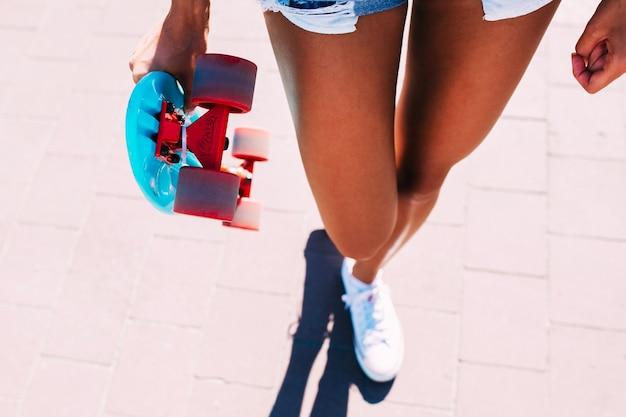 인식 할 수없는 여자 스케이트 보드와 함께 산책