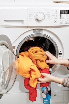 세탁기에서 더러운 세탁물을 씻는 알아볼 수 없는 여자
