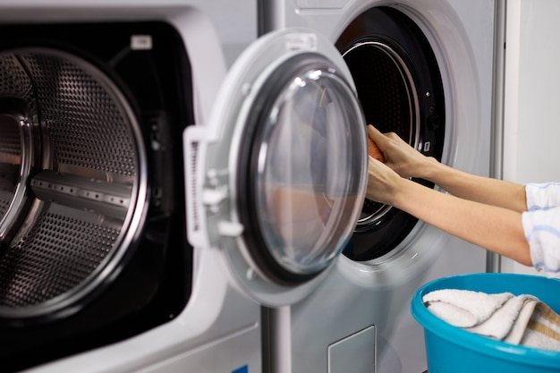 Unrecognizable woman in washing house sorting clean clothes, doing household duties, woman pulls out clothes from washing machine, holding basin
