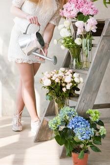 生花の花束に水をまく認識できない女性。若い花屋は新鮮な花束を持ってフラワーショップで働いています。結婚式のための美しい装飾