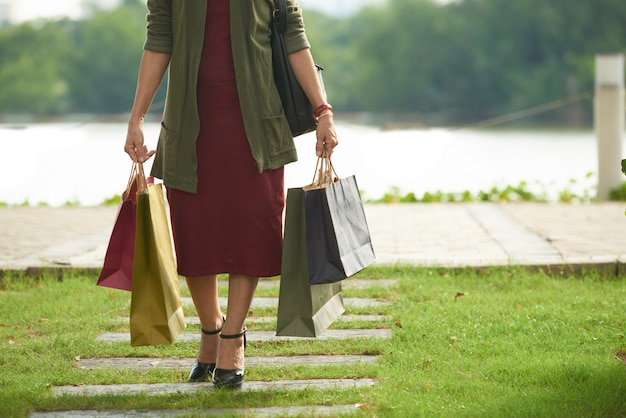 Unrecognizable woman wearing stylish outfit walking with shopping bags