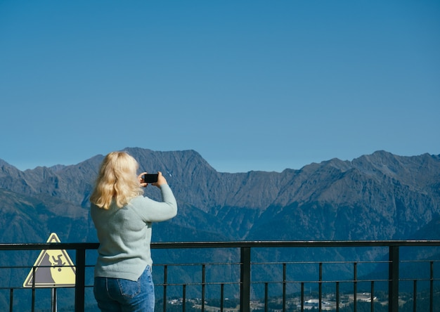 Unrecognizable woman with backpack standing on observation deck in mountains