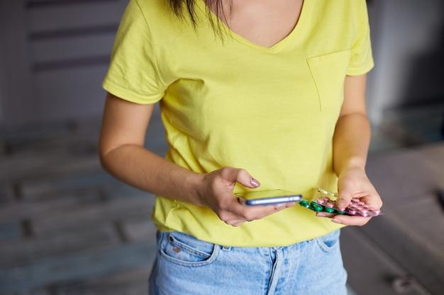 手に錠剤とスマートフォンのブリスターパックを持つ認識できない女性