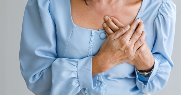 Unrecognizable woman with sudden heart attack and hold chest. concept of emergency health care and affected from congestive failure or cardiopulmonary resuscitation, heart problem.