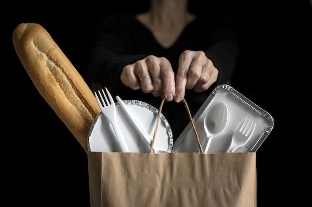 テイクアウトのフードバッグを持つ認識できない女性。食べる準備ができている食品。配達