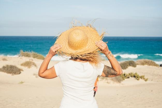 人のいないビーチを楽しんで海を見ている観光帽子をかぶった認識できない女性