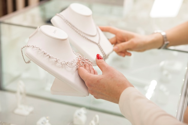 Неузнаваемые женщины выбирают бриллиантовые ожерелья в ювелирном магазине