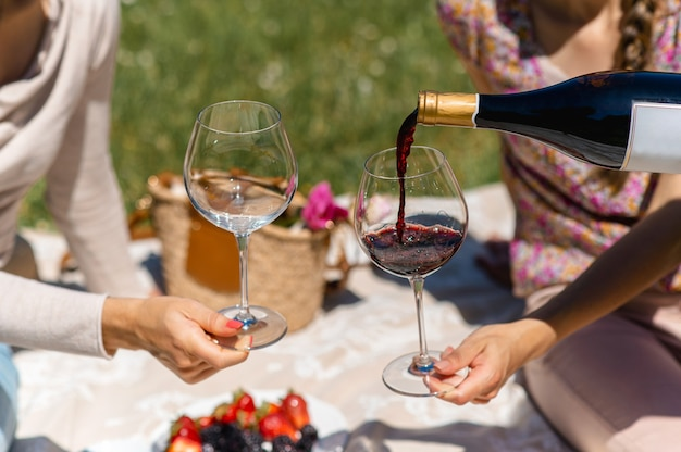 Unrecognizable women sitting on a blanket having picnic. female pouring red wine into a glass. fruits on background.