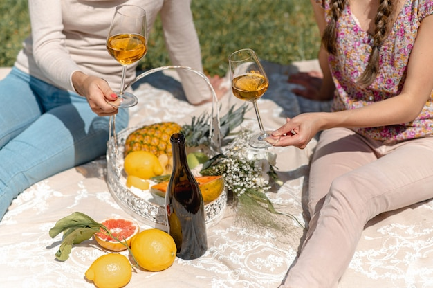 Unrecognizable women sitting on a blanket having picnic. females showing wineglasses full of white wine. tropical fruits on basket, flowers and a bottle.