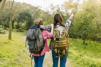 Unrecognizable women with backpacks pointing at distance