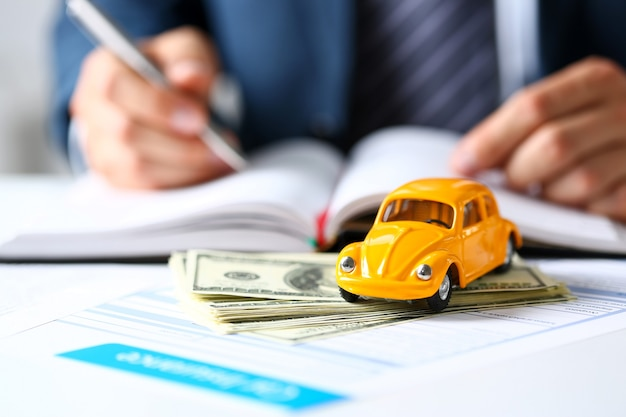 Unrecognizable yellow car on selling documents and pack of dollars closeup with employee holding silver pen. driver money loss prevention, carrier office, road trip, offer legal care