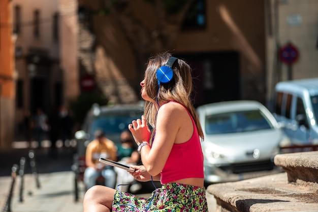 도시에서 계단에 앉아 긴 머리를 가진 인식 할 수없는 젊은 금발 소녀. 그녀의 휴대폰과 헤드폰으로 음악을 듣고 있습니다.