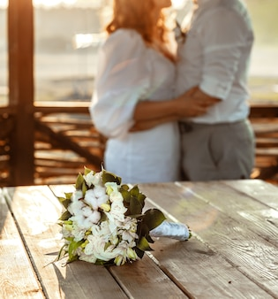 До неузнаваемости молодая пара держится за руки во время романтического свидания в прекрасном летнем кафе, букет белых роз, лежащих на деревянном столе