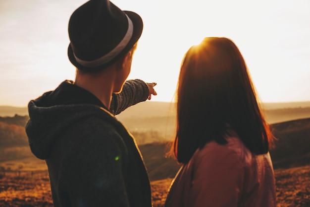 인식 할 수없는 젊은 부부는 함께 시골 필드에 서있는 동안 장엄한 일몰 하늘을보고. 일몰을 감상하는 젊은 부부