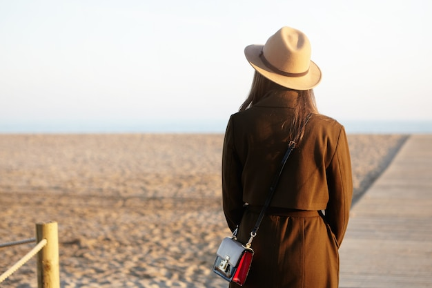 Unrecognizable young female wearing stylish hat, coat and shoulder bag contemplating amazing view