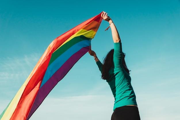 푸른 하늘 벽으로 그녀의 머리 위에 게이 프라이드 깃발을 올리는 인식 할 수없는 어린 소녀