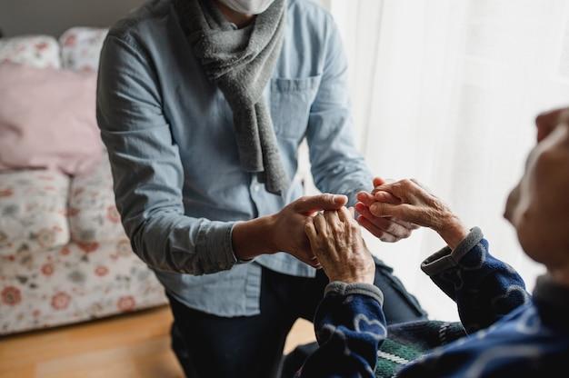老婆の手をつないで認識できない若い男。高齢者、介護、家族の概念。