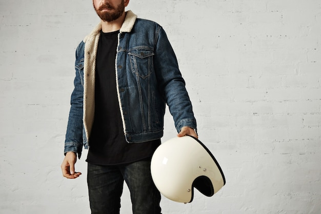 Unrecognizable young motor biker wears shearling denim jacket and black blank henley shirt, holds vintage beige motorcycle helmet, isolated in center of white brick wall