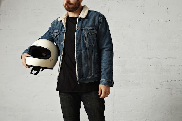Unrecognizable young motor biker wears shearling denim jacket and black blank henley shirt, hugs his vintage beige motorcycle helmet, isolated in center of white brick wall