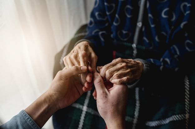 До неузнаваемости молодой человек, взявшись за руки старухи. пожилые люди, уход, концепция семьи.