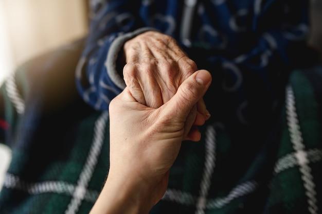 老婆の手をつないでいる認識できない若い人。高齢者、介護、家族の概念。