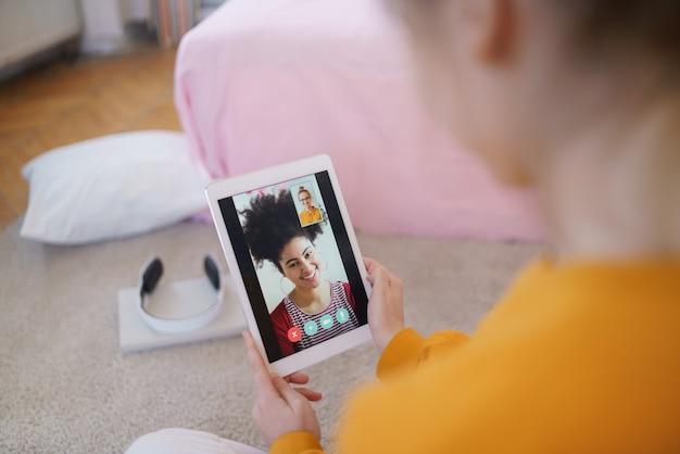 タブレットを持って家に座ってビデオ通話をしている認識できない若い学生の女の子。