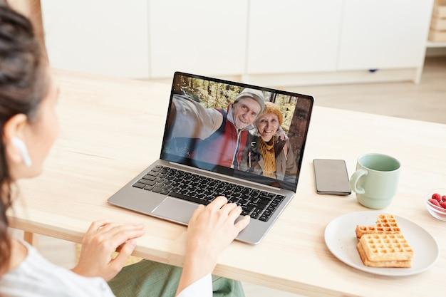 До неузнаваемости молодая женщина получает видеозвонок от родителей на ноутбуке, сидя за столом у себя дома