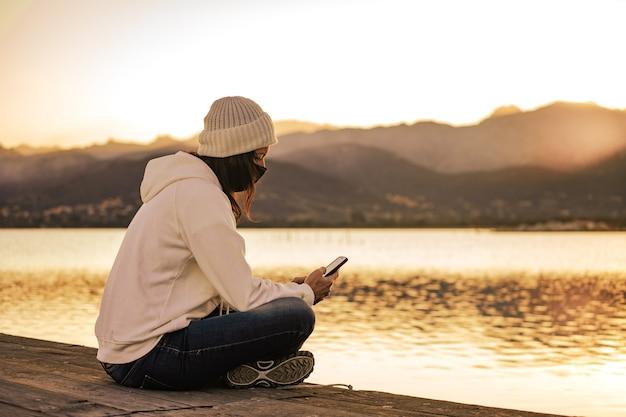 코로나바이러스 사회적 거리로 인해 스마트폰을 사용하여 보호용 얼굴 마스크를 쓰고 혼자 부두에 앉아 있는 흰색 모직 모자를 쓴 알아볼 수 없는 젊은 여성