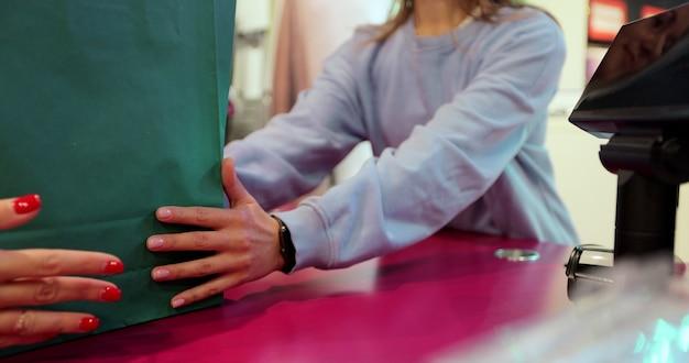 알아볼 수 없는 젊은 여성이 매장의 현금 데스크에서 고객에게 쇼핑백을 전달합니다. 쇼핑 센터나 쇼핑몰에서 고객에게 서비스를 제공하는 백인 여성 점원. 무역 및 서비스 개념입니다.