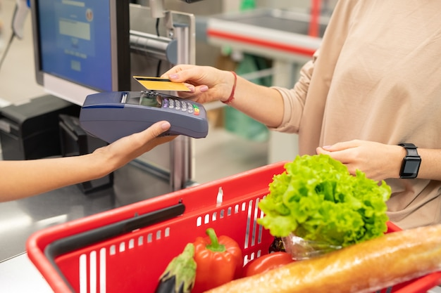 Unrecognizable young woman paying for foods in modern supermarket with credit card
