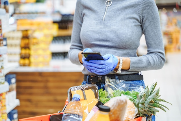 Unrecognizable young woman in protective gloves shopping and browsing the internet on her smartphone, checking discounts or typing sms in a supermarket