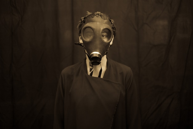 Unrecognizable young woman in scary gas mask looking at camera while standing