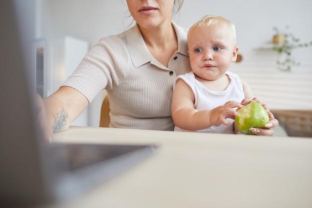 До неузнаваемости молодая женщина сидит за столом и работает на ноутбуке, пока ее ребенок сидит у нее на коленях