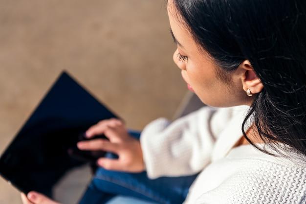 태블릿을 사용하여 거리에 앉아 있는 알아볼 수 없는 젊은 여성