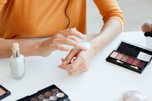 Unrecognizable young woman testing new beauty product on her hand, horizontal high angle close up shot