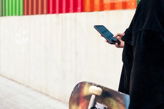 그녀의 손에 스케이트보드를 들고 거리를 걷고 있는 동안 휴대폰에 타이핑하는 알아볼 수 없는 젊은 여성