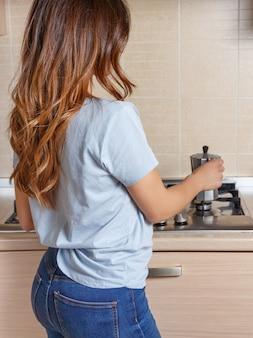 キッチンで朝のエナジードリンクを淹れるためにコンロモカコーヒーメーカーを使用している認識できない若い女性。自宅で朝食に芳香飲料を準備している白人主婦