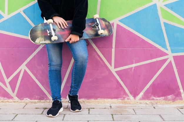 화려한 벽에 기대어 스케이트보드를 탄 알아볼 수 없는 젊은 여성