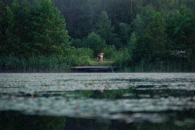 Unrecognizble naked woman changes clothes on a shore of a pond after bathing in summer evening