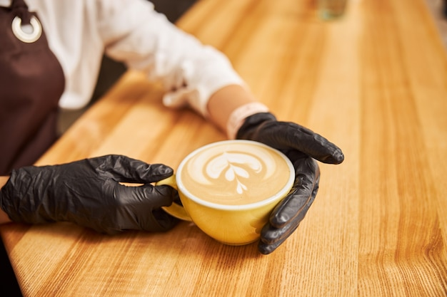 Unrecognized barista in black rubber gloves placing a cup of cappuccino on a wooden bar counter